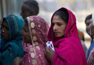 A women wait in a queue to cast their votes at a polling booth in New Delhi.