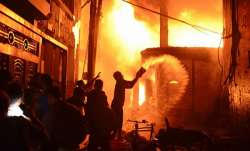 Firefighters and local people help to douse a fire in