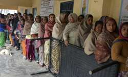 Voters standing in a queue at a polling booth to cast their