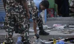 Nepalese army personnel examine the site of an explosion in
