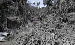 residents walk at their volcanic ash covered village in Laurel, Batangas province, southern Philippi