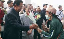 Cambodia's Prime Minister Hun Sen, left, gives a bouquet of flowers to a passenger who disembarked f