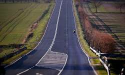 A man rides his bicycle on an empty road in the Taunus region near Frankfurt, Germany, Saturday, Mar