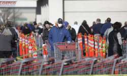 A person wears a mask as he stands in line at Costco Saturday, April 4, 2020, in Salt Lake City. The