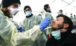 In this March 23, 2020, file photo, medical employees demonstrate testing, at a coronavirus test cen