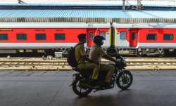 Policemen patrol on a bike along a stationed train during