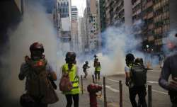 Members of the media take cover as police fire tear gas during a protest against Beijing's national