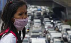 A woman wearing a protective mask looks as traffic builds up during the first day of a more relaxed