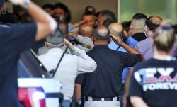 People salute as the body of a McAllen Police officer is carried out at McAllen Medical Center, Sat