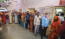 Voters stand in a queue to cast their vote at a polling