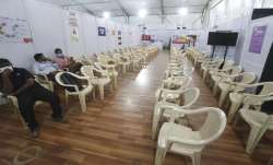 Health workers sit in the waiting area of vaccination
