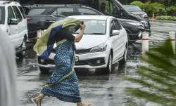 A parliamentary staff looks for cover as it rains in Delhi.