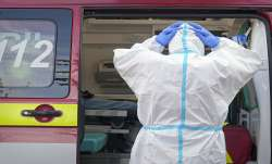 A paramedic adjusts his protection equipment outside the