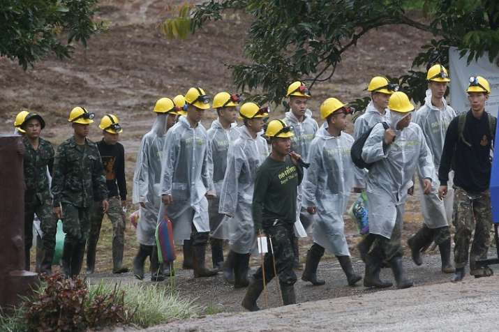 Rescuers walk toward the entrance to a cave complex where