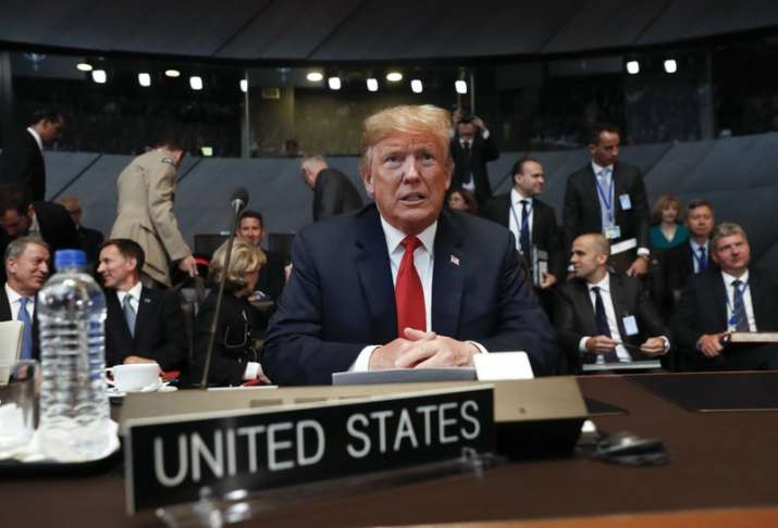 US President Donald Trump takes his seat as he attends the