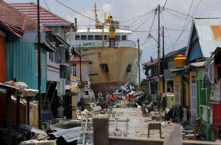 A ship rests near houses after it was swept ashore during