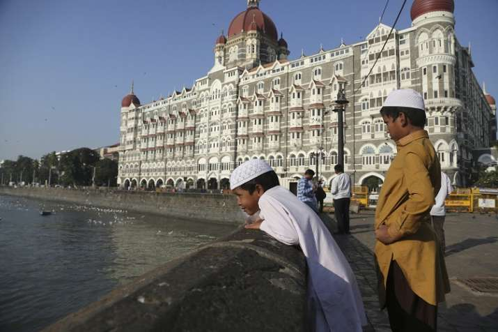 Two boys stand outside the iconic Taj Mahal Palace hotel,