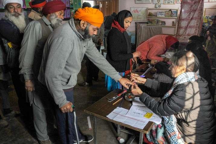 An election officer puts indelible ink mark on the finger