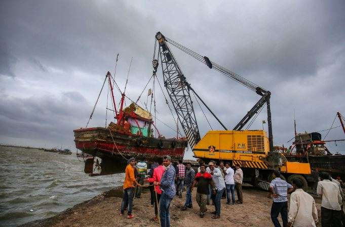 A crane lifts a boat from the shore to move it to a safer