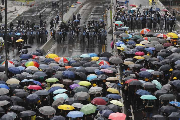Protesters holding umbrellas face off police officers in anti-riot gear in Hong Kong on Monday, July