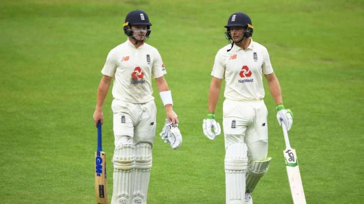Ollie Pope and Jos Buttler of England leave the field as