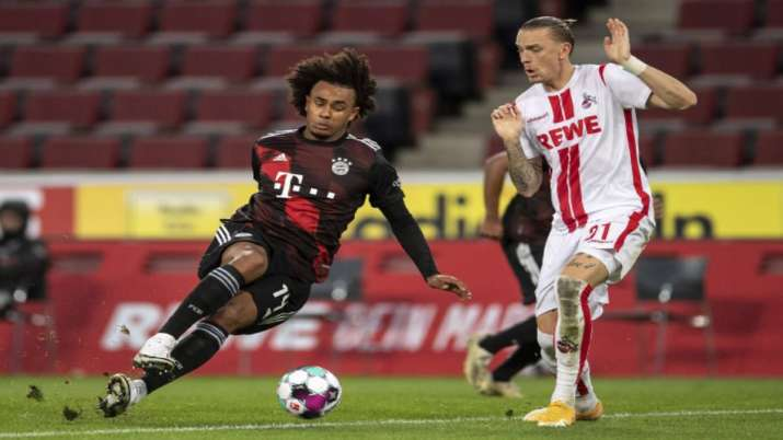 Bavaria's Joshua Zirkzee, left, stumbles next to Cologne's