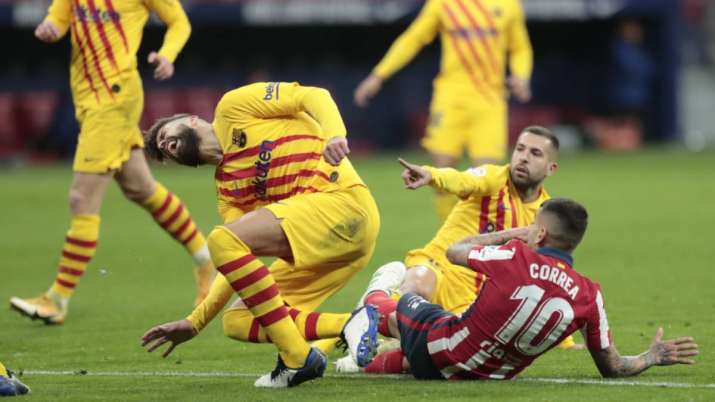 Barcelona's Gerard Pique, left, reacts after getting an