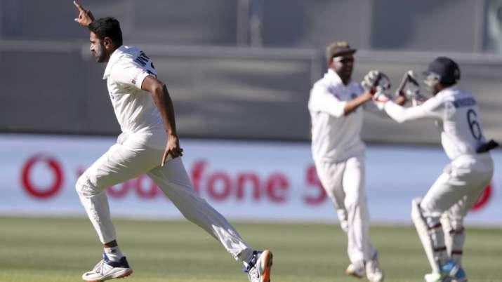 India's Ravichandran Ashwin, left, celebrates taking the