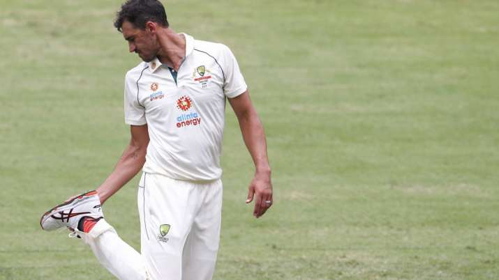 Australian bowler Mitchell Starc checks his boot during
