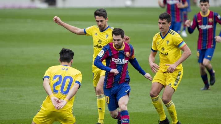 Barcelona's Lionel Messi, center, controls the ball during