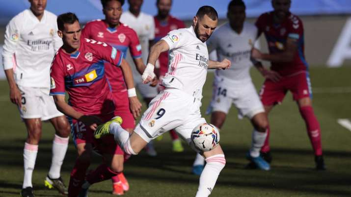 Real Madrid's Karim Benzema kicks the ball next to Elche's