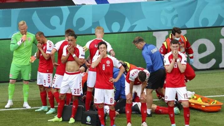 Denmark players react while medics assist their teammate Christian Eriksen