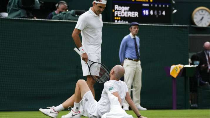 Switzerland's Roger Federer talks to Adrian Mannarino of
