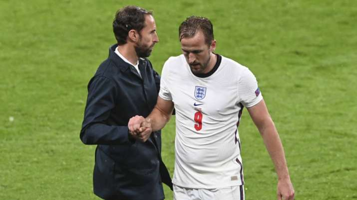 England's Harry Kane, right, shakes hands with his coach