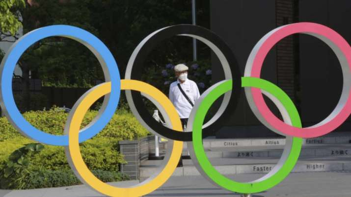 A man walks past the Olympic rings in Tokyo, Monday, June
