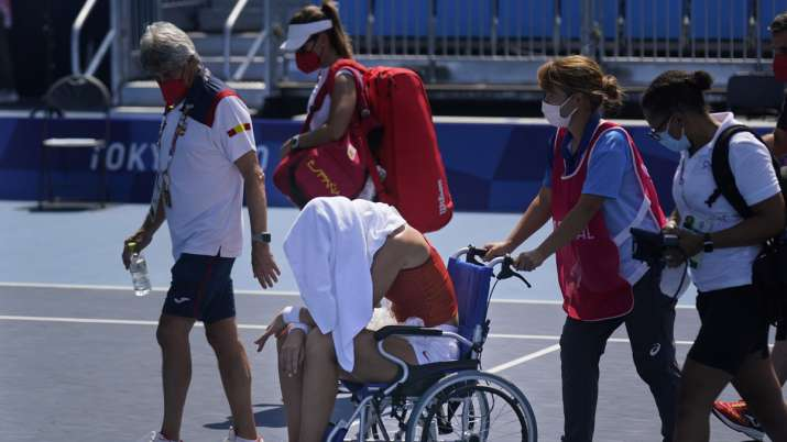 Paula Badosa, of Spain, is helped off the court in a