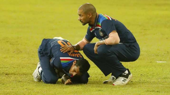 India's Navdeep Saini holds his arm in pain as Shikhar Dhawan attends during second T20I against Sri