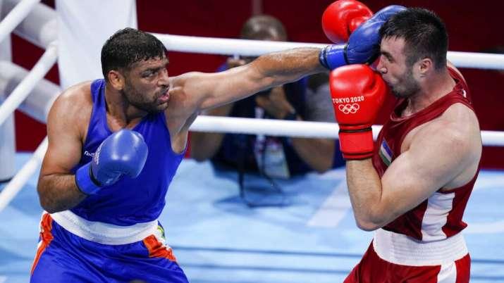 India's Satish Kumar, left, punches Uzbekistan's Bakhodir Jalolov