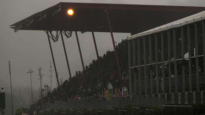 Spectators wait under an overhang during a rain delay at