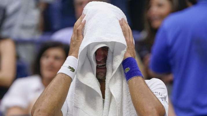 Novak Djokovic, of Serbia, cries as he sits on his bench