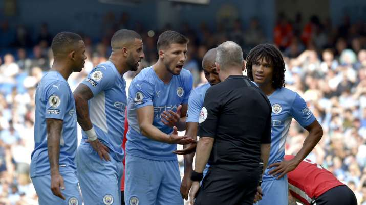 Manchester City players argue with referee Jonathan Moss